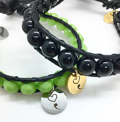 image of two Kirr Bijoux leather cord & bead bracelets against white background; one bracelet has green beads and a silver charm with a semicolon and heart; second bracelet has black beads and a gold charm with a semicolon and heart
