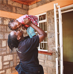 image of ZLT house mother holding one of their children in the air outside the ZLT home