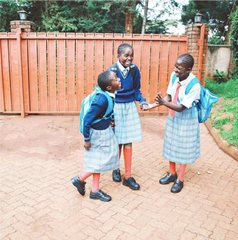 image of three ZLT girls standing outside on brick walkway in their school uniforms