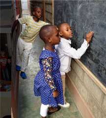 image of three ZLT children standing at chalkboard, practicing writing their names