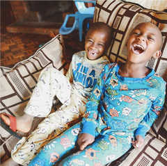 image of two ZLT boys wearing their pyjamas, sitting together on a chair, laughing