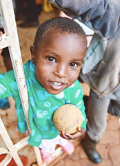 image of a child from ZLT, looking up at camera and holding a ball in her left hand