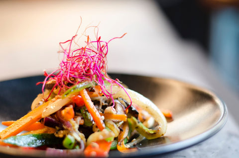 image of soft taco piled high with quick pickled veggies, sitting on dark grey plate
