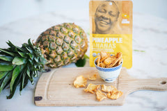 small bowl of dried pineapple sitting on wooden cutting board, with a few pieces of pineapple on the board beside the bowl... bag of dried pineapple and whole fresh pineapple on its side in the background