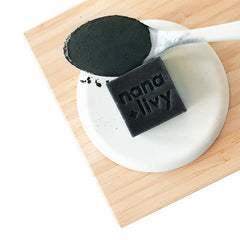 small square black soap block stamped with nana + livy, sitting on white plate on top of wooden cutting board, beside white spoon filled with charcoal powder