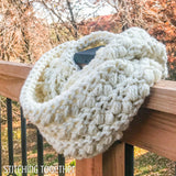 chunky crochet infinity scarf on deck railing