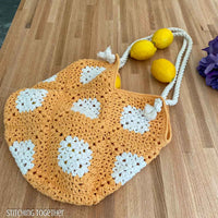 crochet bag filled with lemons spilling out resting on a counter