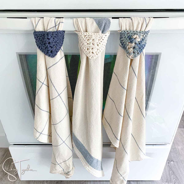 3 dish towels with crochet tops hanging from an oven