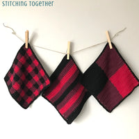 three red, wine and black dishcloths hanging on clothes pins