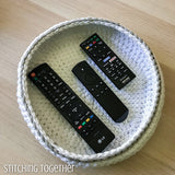 crocheted bowl with tv remotes in it