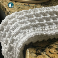 white crochet waffle stitch dishcloth folded on counter