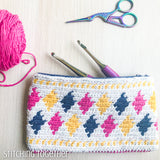 colorful crochet pouch staged with crochet hooks, yarn and scissors