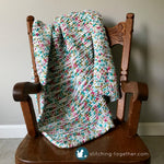 crochet baby blanket draped on small rocking chair