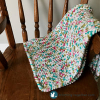 folded squishy crochet baby blanket on arm of rocking chair