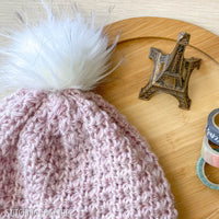 close up of pink crochet hat and pom pom