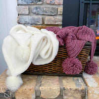white blanket and a red crochet christmas blanket in a basket next to a fireplace