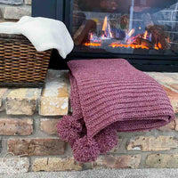 folded christmas crochet blanket with pom poms on the hearth of a fireplace