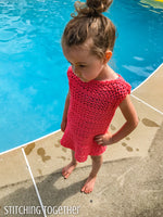 child wearing a crochet girl dress while standing by a pool