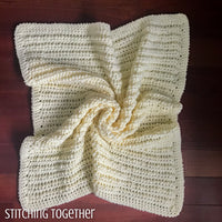 chunky crochet baby blanket spread on the floor