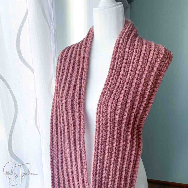 bulky yarn crochet scarf draped on a mannequin