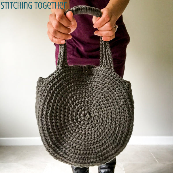 gray crochet circle bag being held