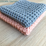 gray and pink crochet washcloths folded