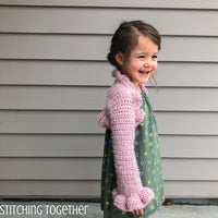 little girl wearing pink crochet bolero with ruffles