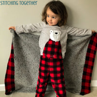 gray and buffalo plaid baby blanket being held by girl