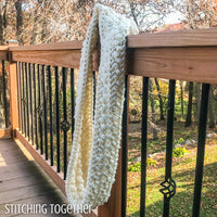 chunky crochet infinity scarf hanging on a deck post