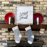 2 crochet christmas stockings hanging on a decorated mantle