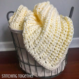 yellow crochet baby blanket in a basket