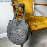 gray circle bag hanging on chair