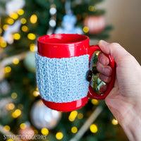 hand holding a red mug with a light blue mug cozy