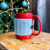 reg mug with blue crochet coffee cup cozy on a table