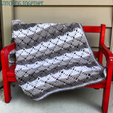 gray and white crochet blanket draped on red bench