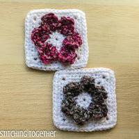 two crochet flower squares one with pink petals on white and one with gray petals on white
