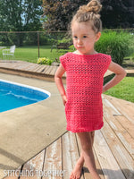 girl wearing a crochet summerdress while standing by a pool