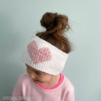 girl wearing crochet heart ear warmer