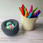 two crochet baskets filled with pens and tape