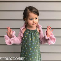 little girl wearing pink crochet shrug with ruffles
