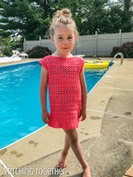 girl wearing a crochet girls dress while standing by a pool
