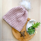 pink crochet beanie hat with pom pom flat lay