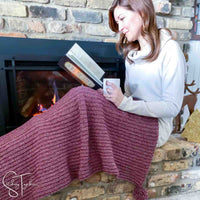 lady reading a book while draped in a marled crochet blanket next to a fireplace