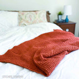 orange crochet blanket draped on the end of a bed