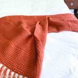 terracotta crochet lap blanket draped on the end of a bed