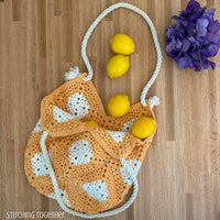 crochet market bag filled with lemons spilling out resting on a counter