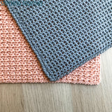 gray and pink crochet washcloths with different textures laying flat