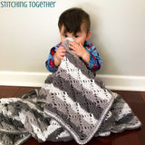 baby holding diamond lace crochet blanket