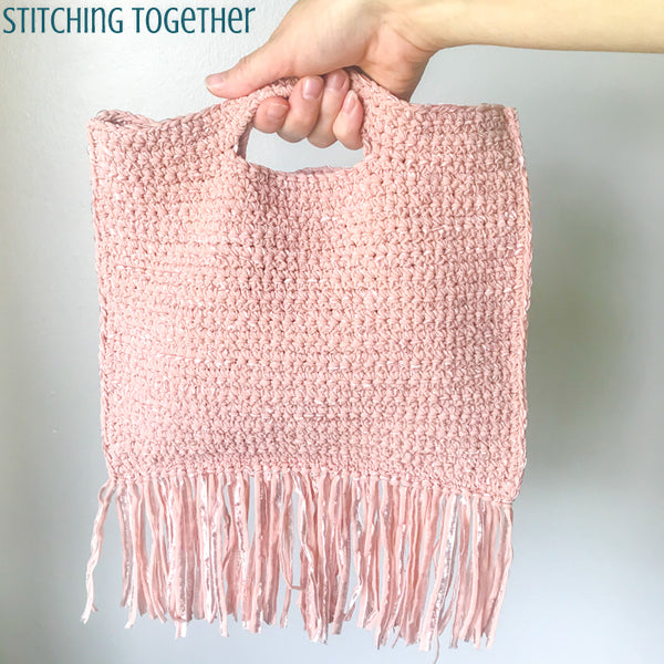 small crochet purse with fringe being held by the handle