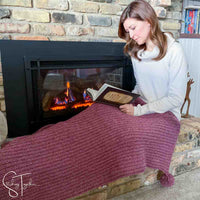 lady reading a book while draped in a red holiday crochet blanket next to a fireplace